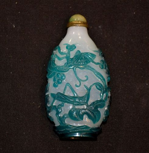 snuff bottle in green and white glass. Carved with praying Mantis