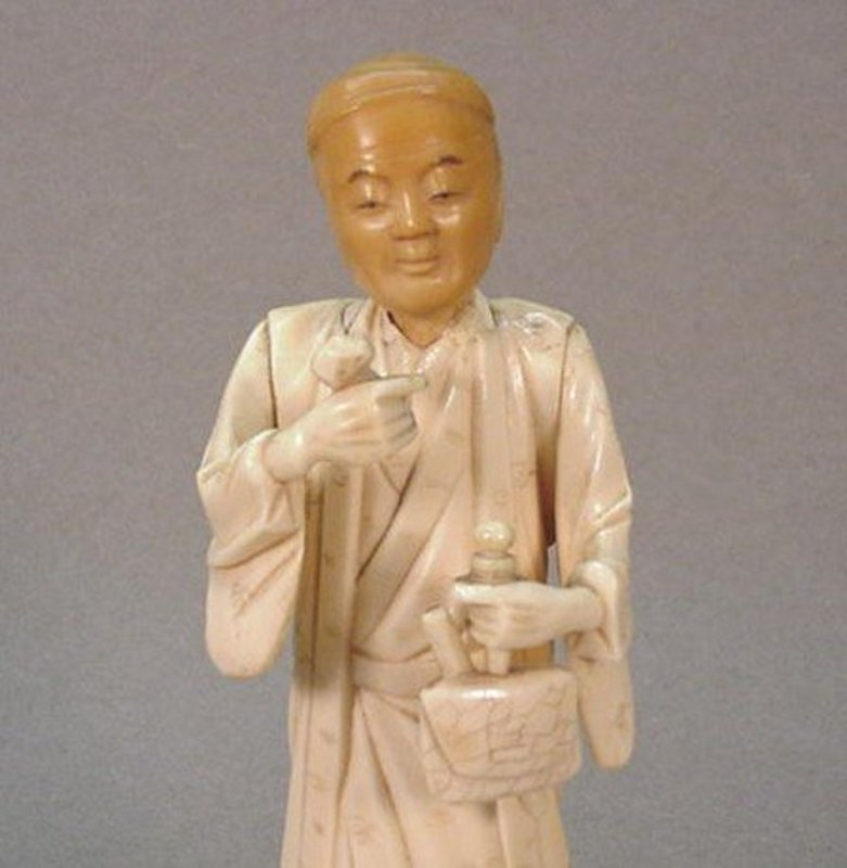 JAPANESE BONE AND TAGUA CARVING OF A MERCHANT