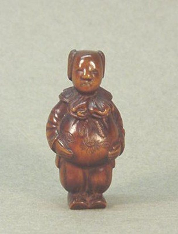JAPANESE CARVED WOOD NETSUKE OF A YOUNG BOY