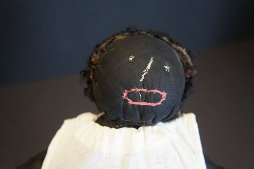 One very unhappy baby, embroidered  face astrakhan hair 1910