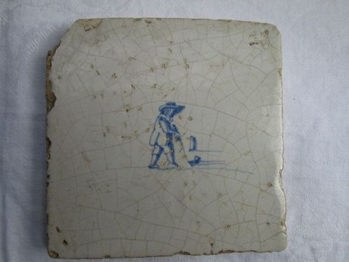 A Dutch delft tile c.1700 depicting a man playing colf.