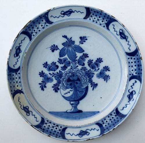 Delft charger centering a vase of flowers 18th c. Dutch