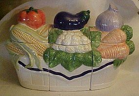 Three piece ceramic canister set with fresh vegetables