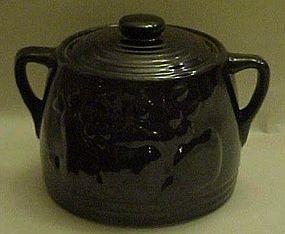 Old black glaze bean pot with fruit